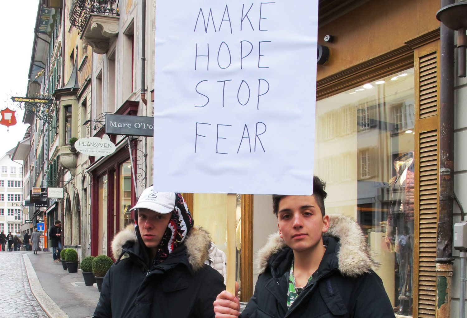 "Two boys hold up a sign saying ""Make Hope Stop Fear"""